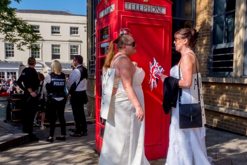 Zwei Frauen in Brautkleidern vor einem roten Telefonhäuschen.