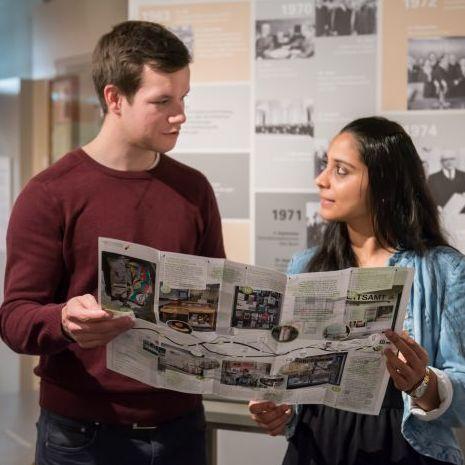 Besucher lesen die Wanderkarte 'Sehnsucht' in der Dauerausstellung in Leipzig