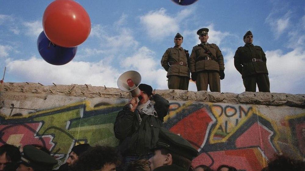 Fotografie von Luftballons in der Luft und Grenzsoldaten, die auf der Mauer vor dem Brandenburger Tor stehen.