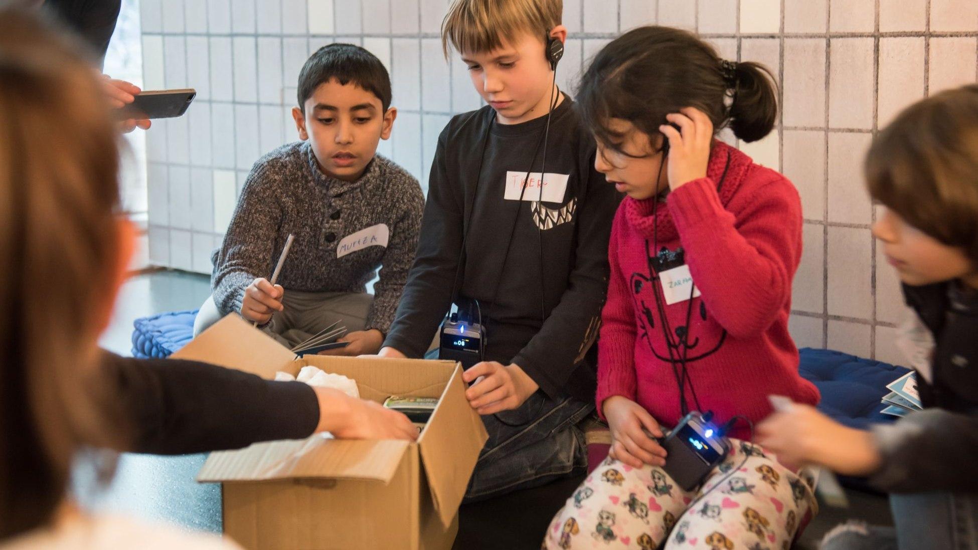 Drei Jungen und ein Mädchen knien vor einem geöffneten Paket