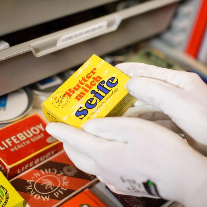 Zwei Hände in weißen Handschuhen halten eine kleine gelbe Pappschachtel mit der Aufschrift Buttermilchseife. Darunter liegen in einer Schublade weitere bunte Schachteln.
