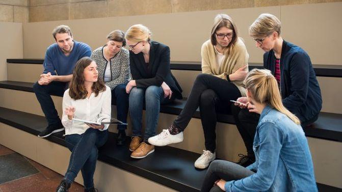 Eine Gruppe Besucher sitzt auf den Treppenstufen im Tränenpalast