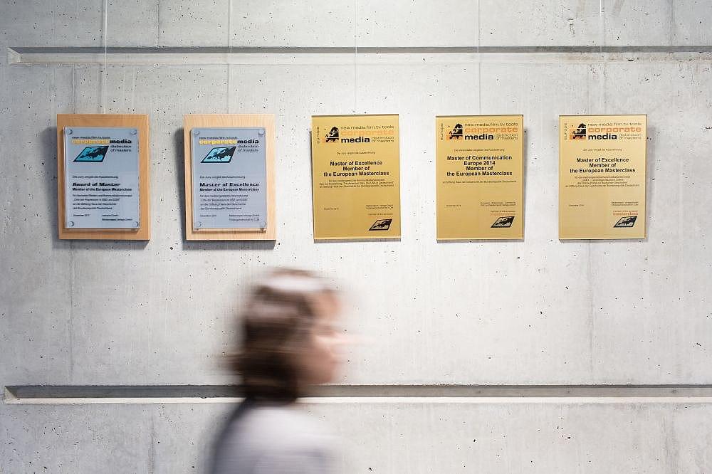 Eine Rand mit 5 Urkunden, zwei davon gerahmt, drei aus Messing, davor eine verschwommene Person