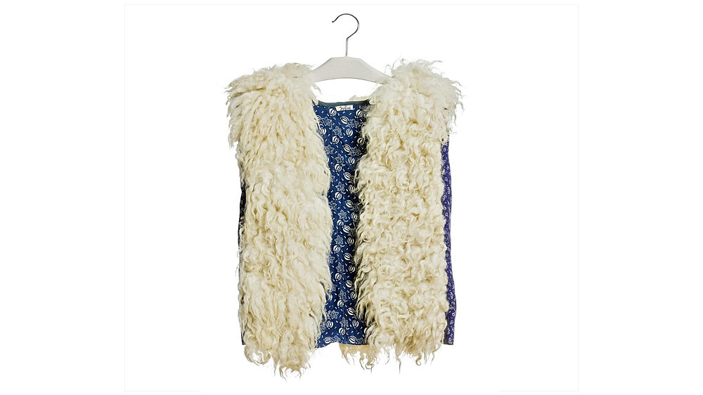 Weste aus floral gemustertem Blaudruckstoff, senkrecht in breiten Bahnen besetzt mit weißem Schaffellimitat; Labeleinnäher am Nacken innen, weiß-schwarz 'Josefine'.