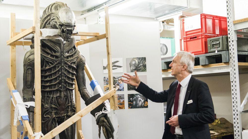 Alien-Figur im Depot mit Begleiter