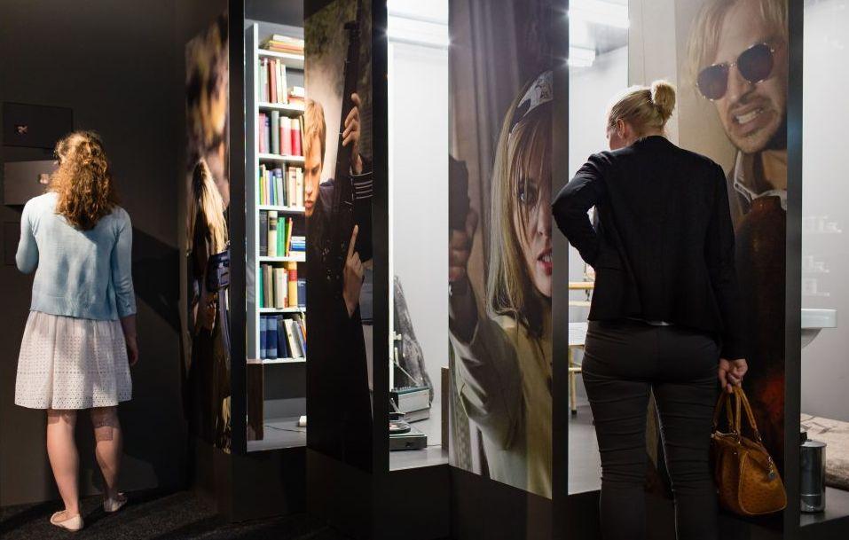 Zwei junge Frauen vor einer Ausstellungswand mit Filmszenen als Fototermine und Durchbrüchen in eine Filmkulisse