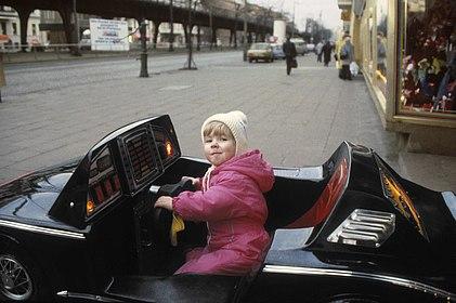 Titelbild zur Ausstellung. Kleines Mädchen sitzt in einem schwarzen Spielauto.