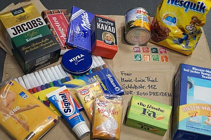 Nahrungsmittel, Hygieneprodukte und Filzstifte liegen auf Packpapier mit einer Dresdner Adresse.