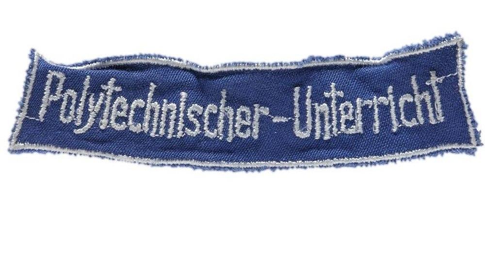 Blauer Aufnäher mit weißem Rand und weißer, gestickter Schrift: 'Polytechnischer-Unterricht'.