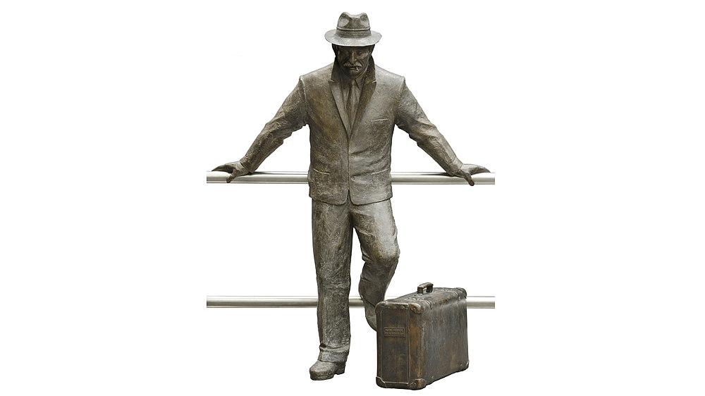 Bronzene Figur eines Mannes mit Hut, Straßenanzug, Hemd und Krawatte. In den Mundwinkeln befindet sich ein Zigarettenstummel. Das linke Bein des Mannes ist angewinkelt.