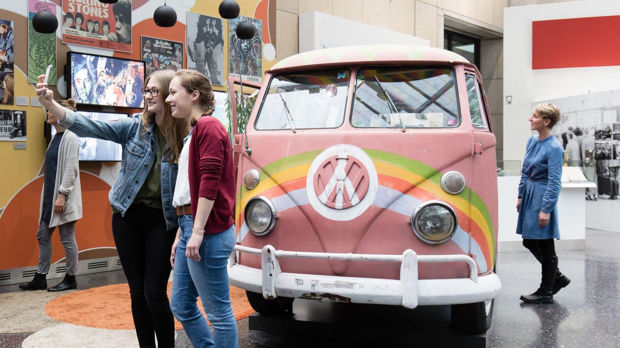 Zwei junge Frauen machen ein Selfie vor einem alten VW-Bus in der Ausstellung, der rosa gestrichen ist und ein Peace-Zeichen sowie einen Regenbogen auf die Front gemalt hat