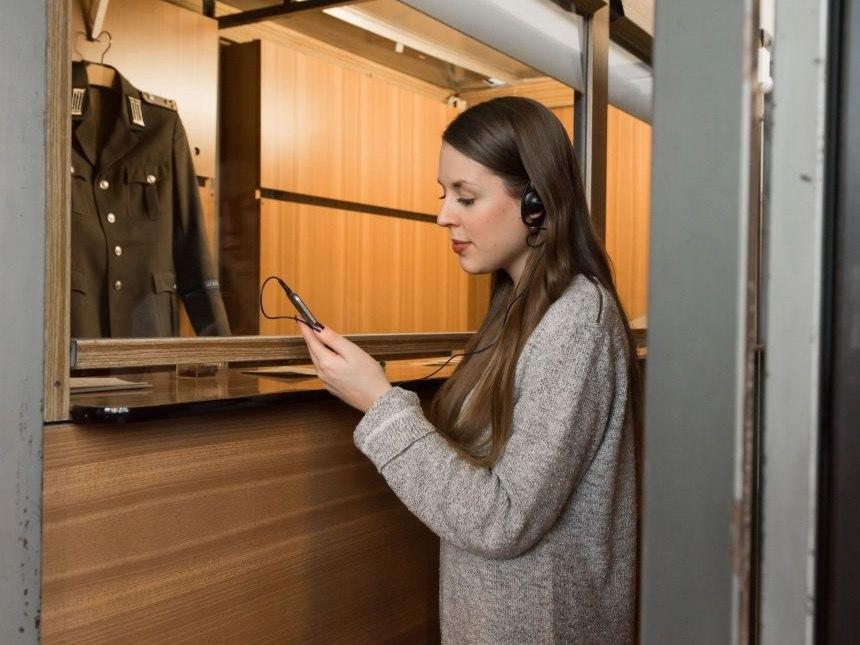 Eine junge Frau steht mit einem Smartphone in der Hand und Ohrhörer in einer ehemaligen Grenzkabine mit Holzverkleidung. Hinter der Glasscheibe hängt eine Uniformjacke