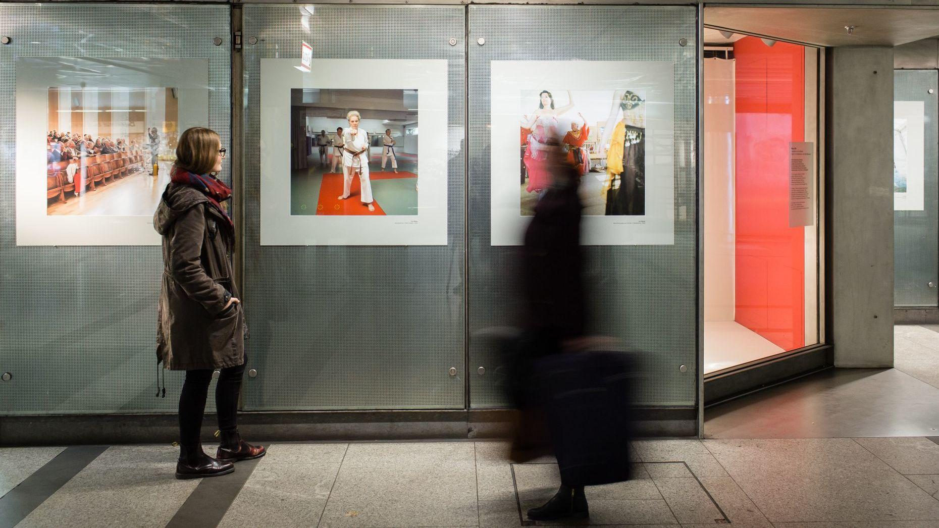 In einer U-Bahn-Station steht eine junge Frau vor einer Wand mit drei großformatigen Fotos und betrachtet sie, eine weitere Frau läuft mit einem Koffer durch das Bild
