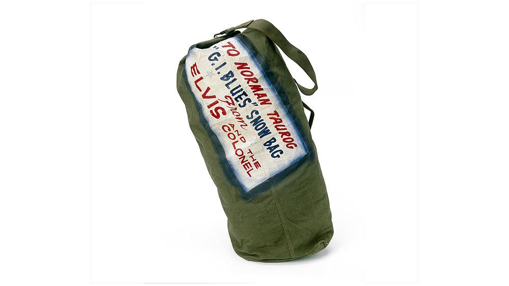 Olivgrüner Seesack (US Army Duffel bag). Trageriemen mit Karabinerhacken und Tragegriff. Daneben die schwarzen Buchstaben: 'U.S.'.