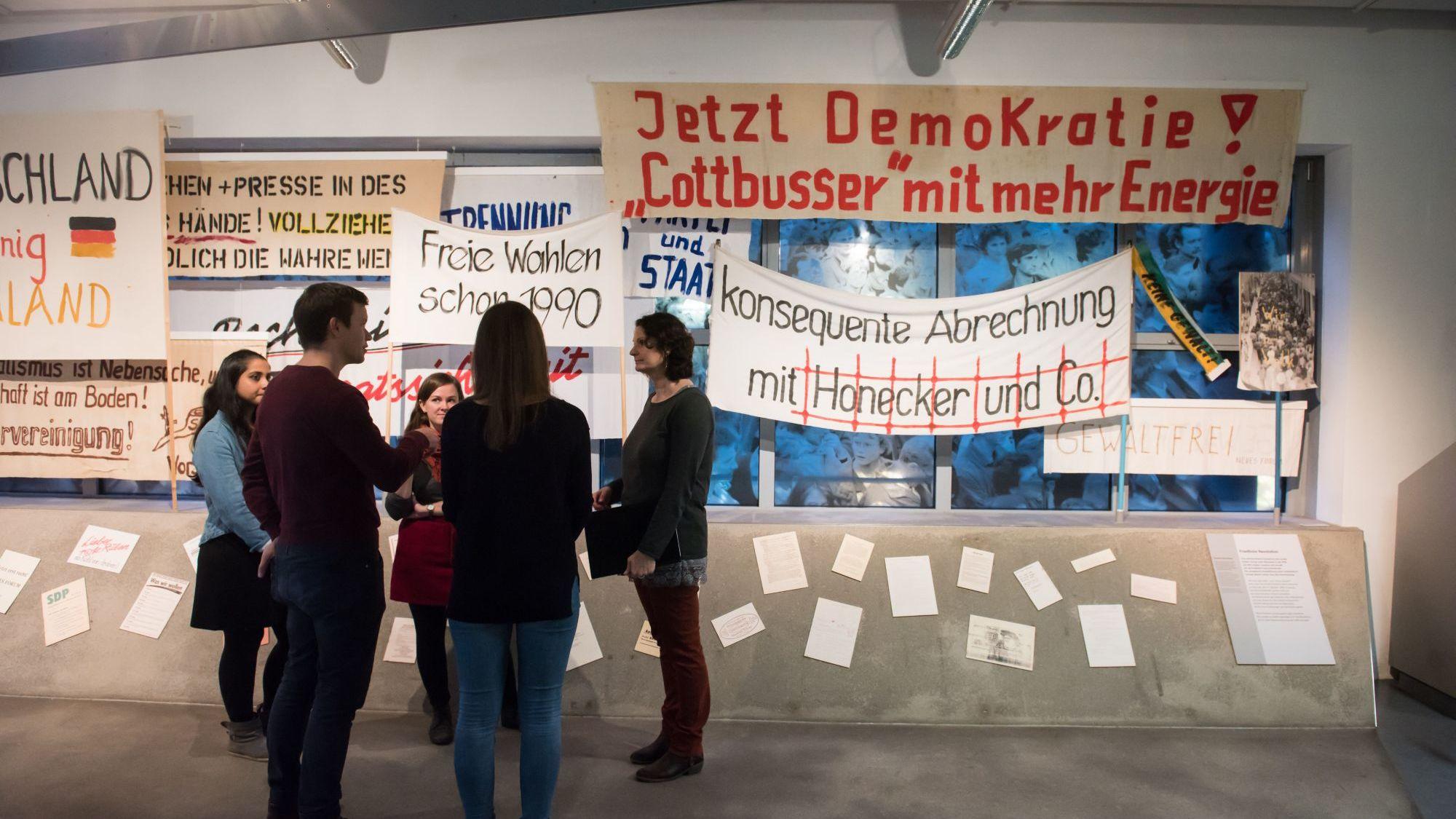 Besucherinnen stehen vor Demonstrationsplakaten