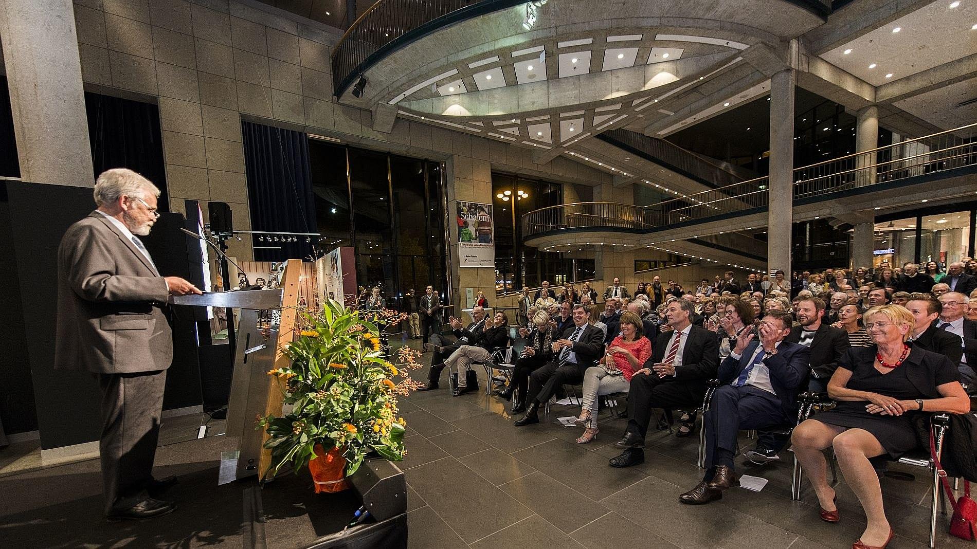 Redner am Pult bei Ausstellungseröffnung im Foyer Haus der Geschichte