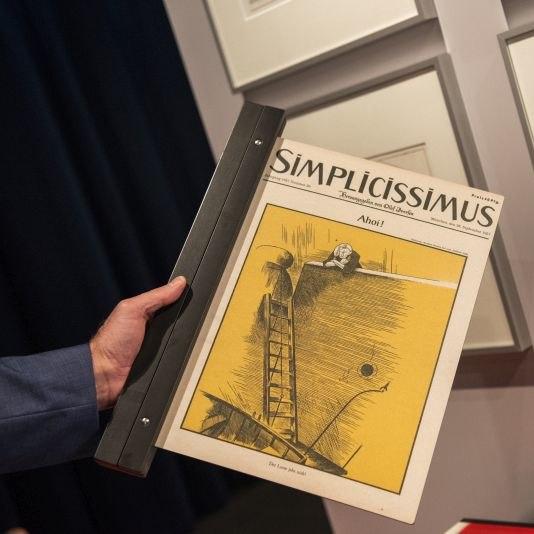 Eine Hand hält eine Ausgabe der Satire-Zeitschrift Simplicissimus