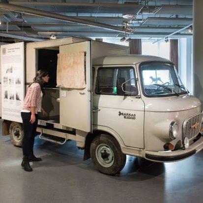 Eine Besucherin betrachtet einen Barkas-Kleintransporter in der Dauerausstellung