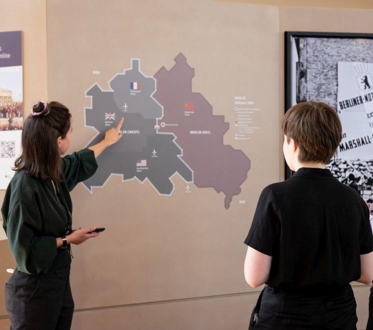 Drei Besucherinnen im Eingangsbereich der Ausstellung.