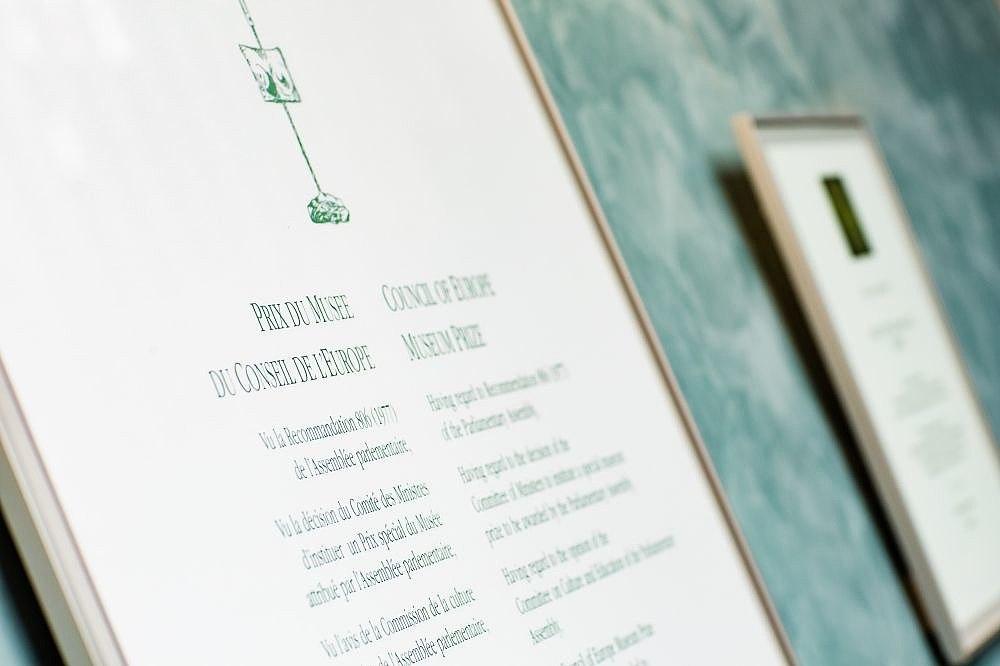 Gerahmte Urkunden hängen an einer türkisgrünen Wand, die eine sehr nahe aufgenommen, die andere im Hintergrund