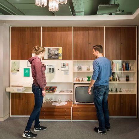 Zwei Besucher betrachten eine typische Schrankwand aus der DDR