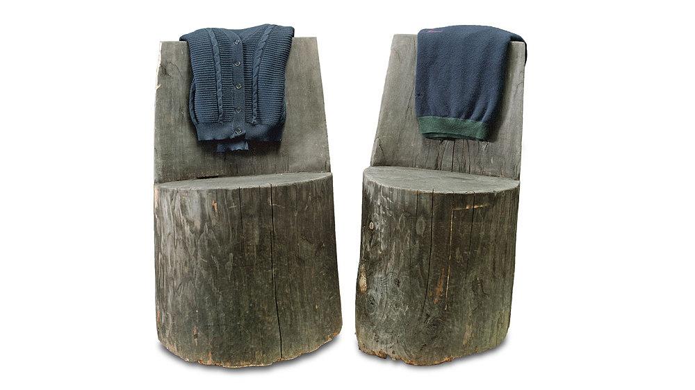 Zwei braune Stühle aus einem Holzstamm gearbeitet.