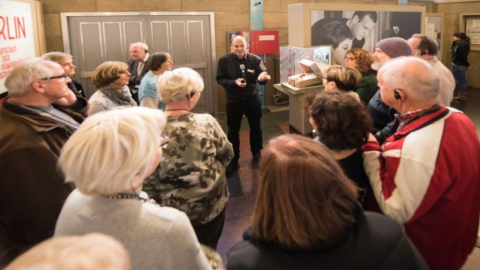 Eine Gruppe Seniorinnen und Senioren hat sich im Halbkreis einem Mann zugewandt, der mit einem Mikrofon in der Hand zu ihnen spricht