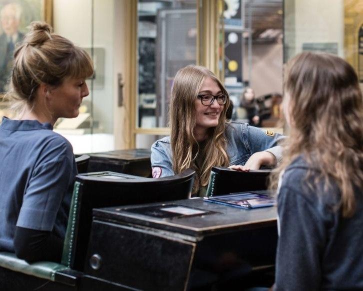 Drei junge Frauen sitzen im Bundestagsgestühl in der Dauerausstellung