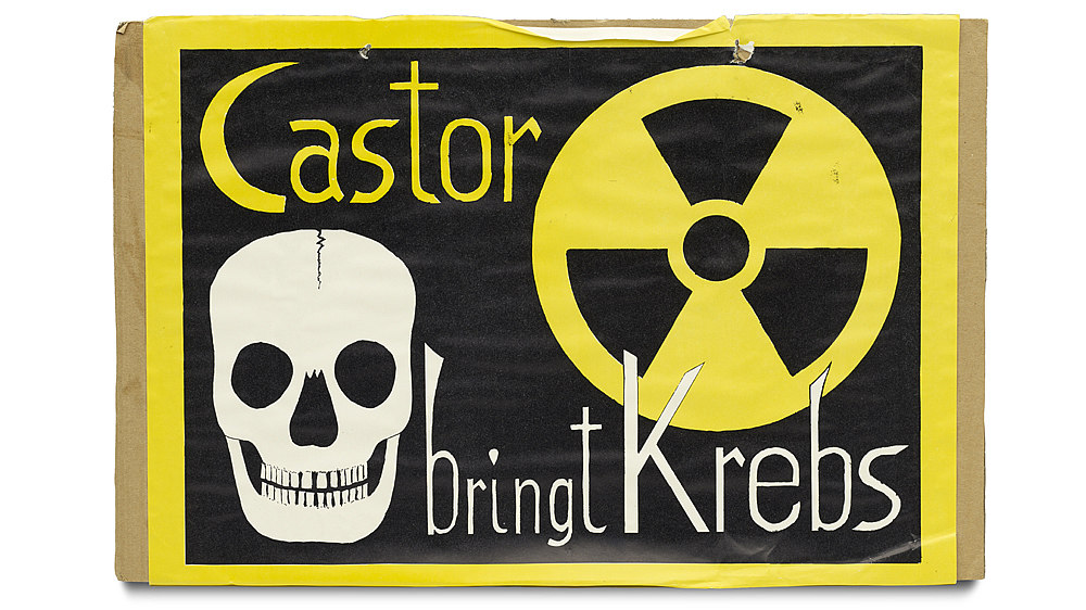 Auf brauner Pappe aufgeklebt: schwarzes Blatt mit gelber Umrandung. Motiv: Totenschädel in schwarz-weiß und das Symbol für Radioaktivität. Dazwischen der Text: 'Castor bringt Krebs'.