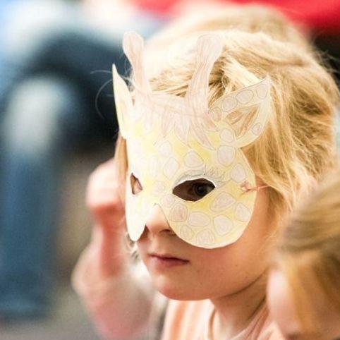 Ein kleines Mädchen mit einer Maske im Haus der Geschichte