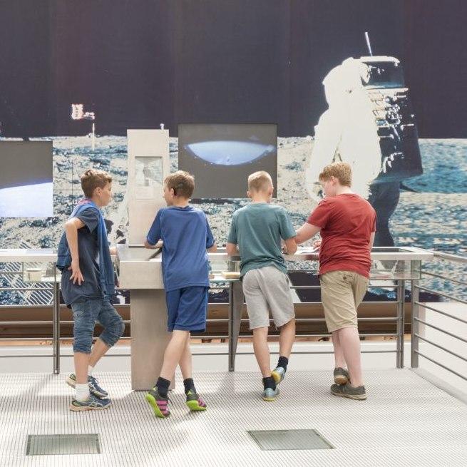 Vier Jungen stehen auf der Mondrampe im Haus der Geschichte