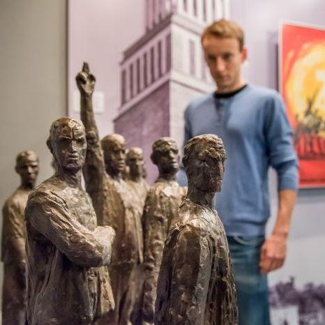 Ein Besucher betrachtet eine Skulptur in der Dauerausstellung in Leipzig