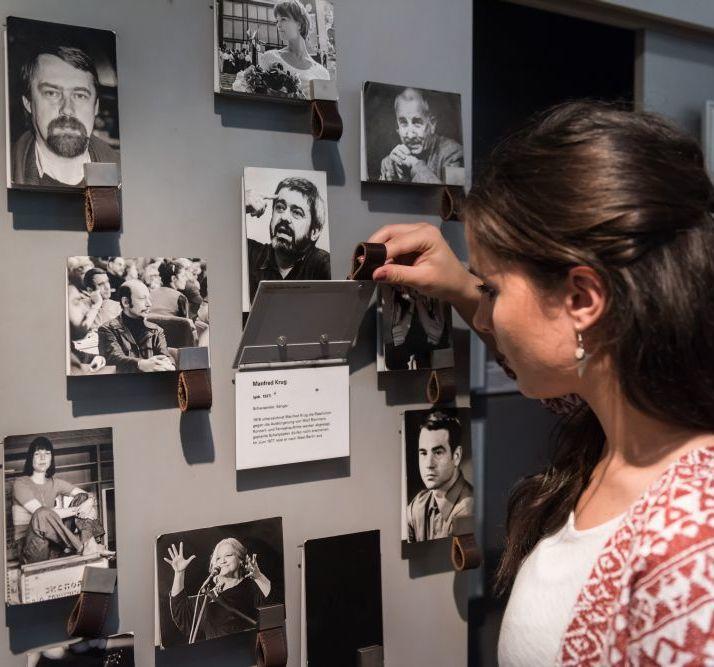 Eine Besucherin betrachtet Fotografien in der Dauerausstellung in Leipzig