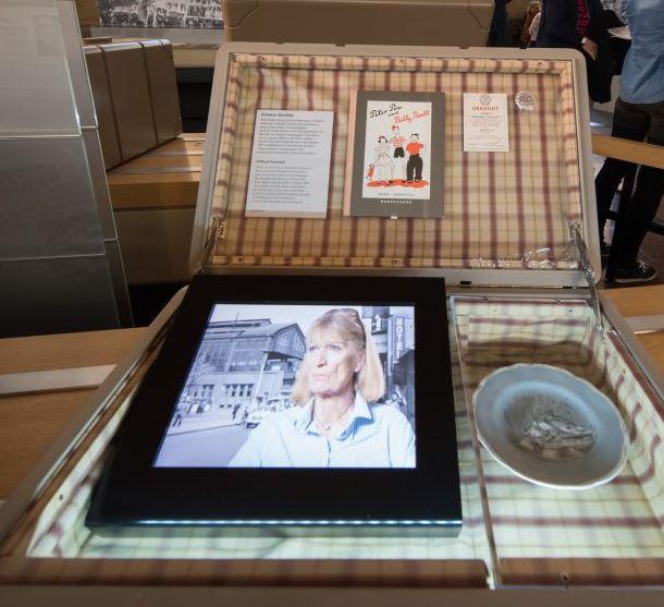 Ein aufgeklappter Koffer, in dem sich ein kleiner Monitor befindet, auf dem ein Film mit einer Frau läuft. Neben dem Monitor im Koffer ein kleiner Porzellan-Teller, darüber ein Kinderbuch. Im Hintergrund Menschen