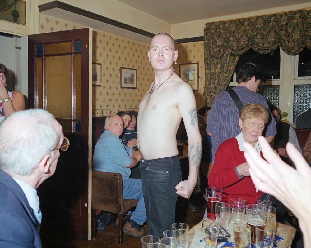 Ein junger Mann steht mit nacktem Oberkörper unter vollbekleideten Gästen und schaut in die Kamera.