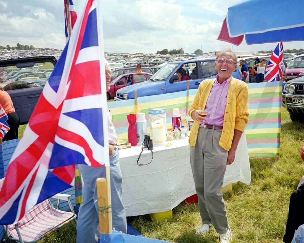 Ein lachender Mann vor einem Picknicktisch, dazu Union-Jack-Flaggen und vielen Autos.