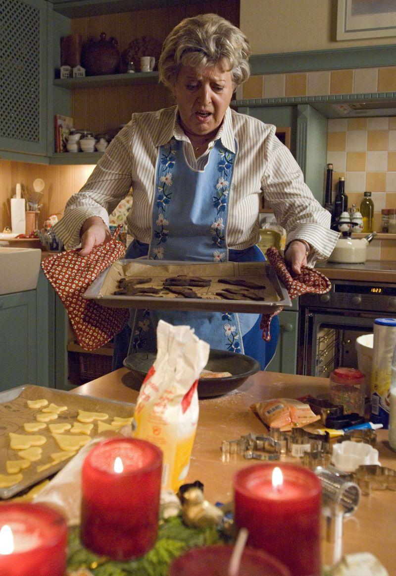 Helga (Marie-Luise Marjan) holt die verbrannten Weihnachtsplätzchen aus dem Ofen