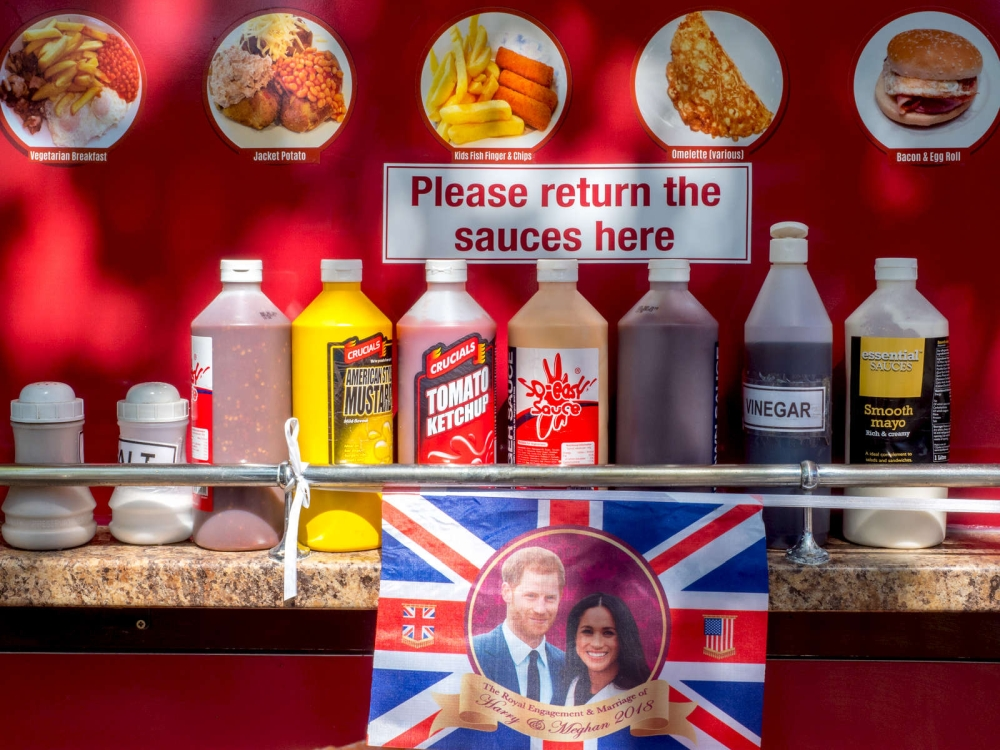 Flaschen mit Fast-Food-Saucen, darüber Essenbilder, darunter ein Union Jack mit einem Foto von Prinz Harry und Meghan Makle.