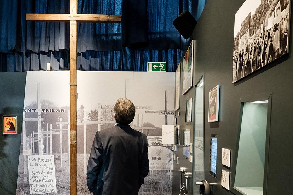 Ein Besucher betrachtet in der Ausstellung ein großes Holzkreuz der Friedensbewegung.