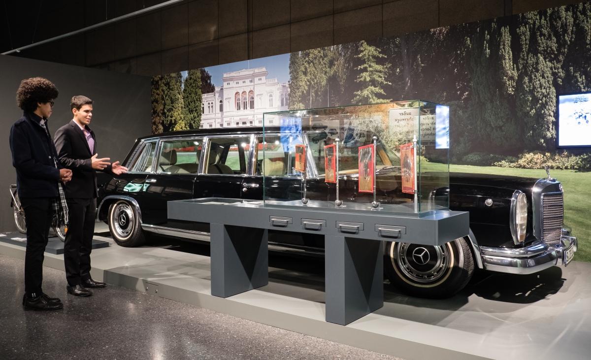 Eine große schwarze Mercedes-Staatslimousine steht in einem Ausstellungsraum vor einem großen Foto der Villa Hammerschmidt, daneben zwei junge Männer.