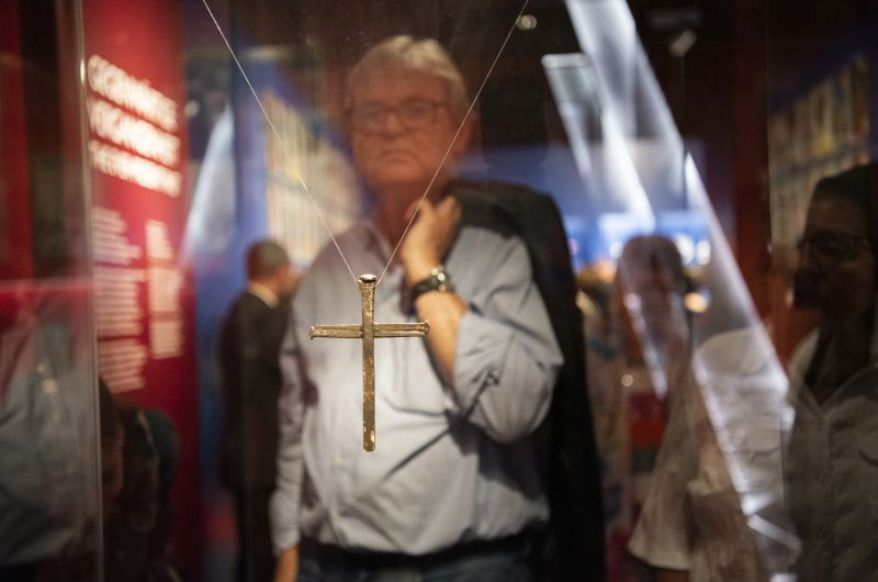 "A visitor is standing behind a display case where the ""Cross of Nails"" form COventry is hanging."
