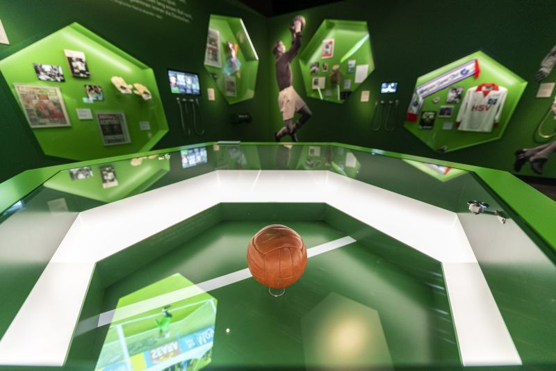 "Green painted exhibition room ""Rivalry and Respect"" with the brown Wembley-Ball in a display-case in the middle."