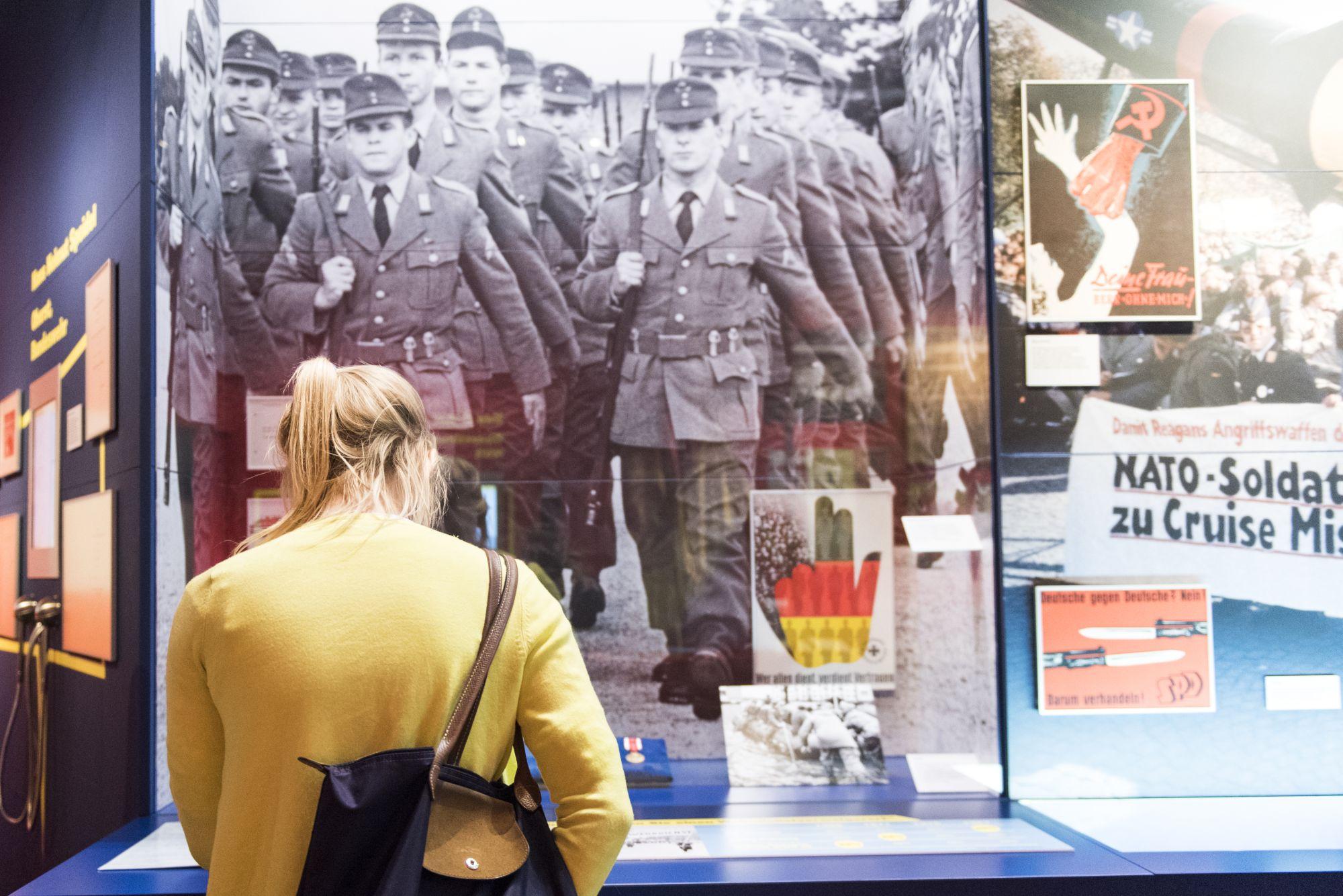 Eine junge Frau in einer gelben Strickjacke mit einer Schultertasche schaut in eine Vitrine, dahinter ein großformatiges Foto von marschierenden Soldaten