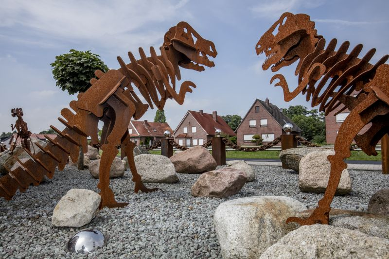 In the foreground are two stainless steel T-Rex dinosaurs looking at a row of detached houses behind them.