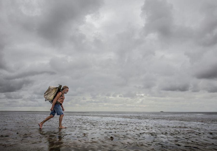 An older man walks through the mudflats with his upper body naked, shorts, and a big backpack.