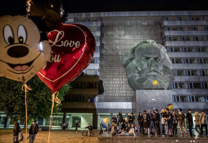 Im Vordergrund sind ein Micky Maus- und ein Herzluftballon zu sehen, im Hintergrund ein Denkmal mit einem großen Marxkopf, auf dessen Sockel Jugendliche feiern.