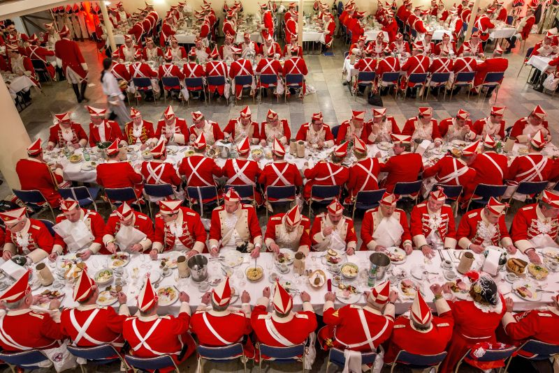 Men in red and white carnival uniforms sit at long tables and eat.