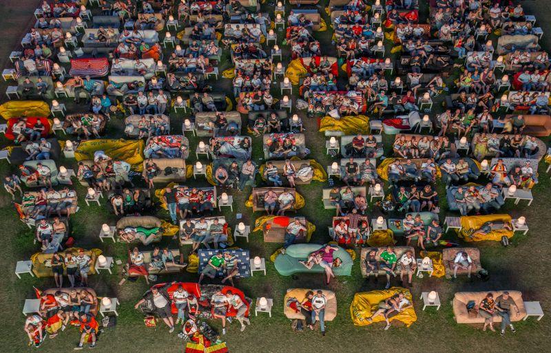 Menschen sitzen auf in Reihen angeordneten Sofas auf einem Rasen, teilweise mit Deutschlandfahnen.