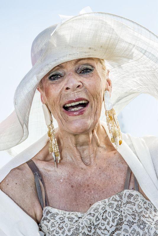 Ältere Dame mit großem, weißem Hut und auffälligen goldenen Ohrringen.