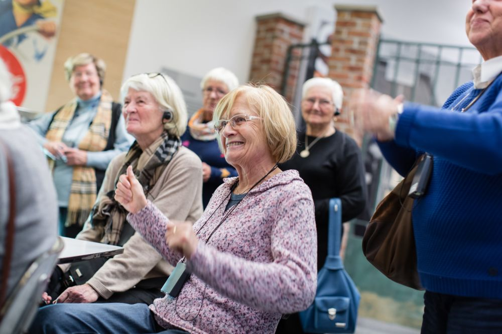 Mehrere Seniorinnen und Senioren sitzen und stehen in der Ausstellung, lächeln und schwingen ihre Arme